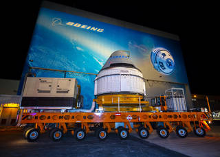 The Boeing CST-100 Starliner spacecraft rolls out from the company's Commercial Crew and Cargo Processing Facility.