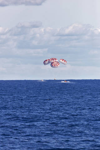 SpaceX's Crew Dragon is guided by four parachutes as it splashes down in the Atlantic Ocean on March 8, 2019