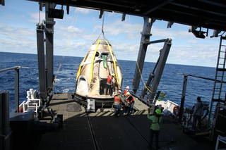 SpaceX's Crew Dragon is loaded onto the company's recovery ship, Go Searcher, in the Atlantic Ocean on March 8, 2019.