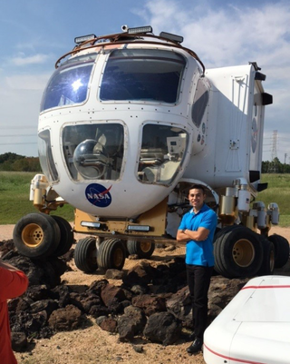 Felipe Valdez poses in front of NASA's Space Exploration Vehicle