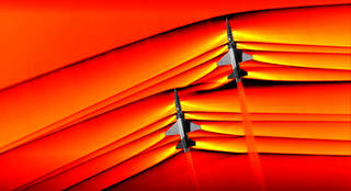 Two U.S. Air Force Test Pilot School T-38 aircraft flying in formation at supersonic speed.