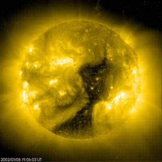 The dark shape sprawling across the face of the active Sun is a coronal hole.