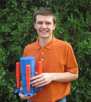 Think Outside the Box Challenge teen group winner Thomas Salverson holds his winning design.