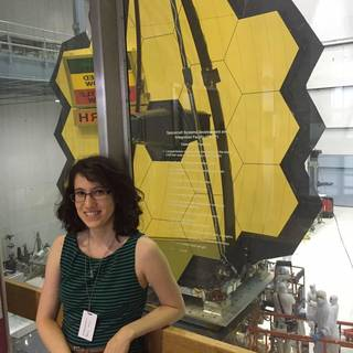 Arney posing in front of the James Webb Space Telescope.