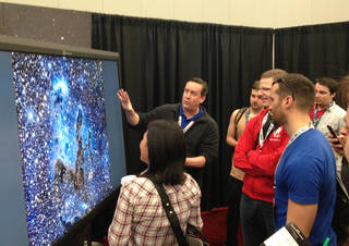 Visitors listen to an explanation of how the Webb telescope will see the famous Eagle Nebula in infrared light at the NASA Booth