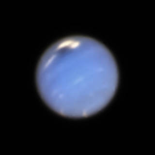 light-blue view of Neptune, seen by Hubble in 2018