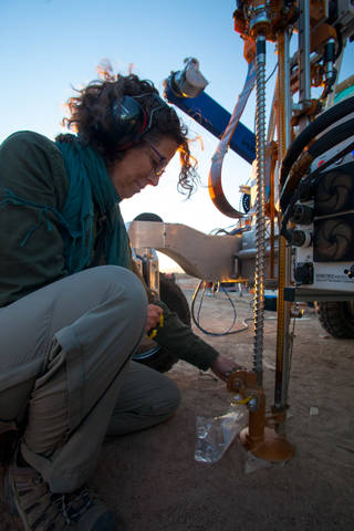 A NASA engineer inspecting the drill attached to the ARADS rover in the desert.