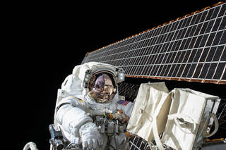Astronaut in spacesuit outside International Space Station with solar array in background
