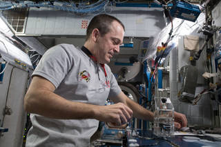 Side view of astronaut Ricky Arnold working with the miniPCR on a work table