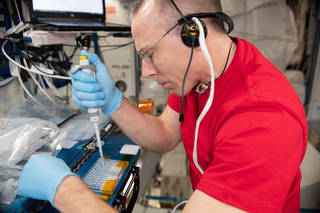 image of astronaut Drew Feustel filling tiny wells for Protein Crystal Growth experiments