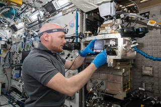 astronaut Alexander Gerst installing hardware inside the space station