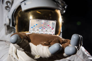image of astronaut in space suit holding tissue chips hardware in gloved hand