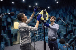 two engineer setting up astrobee satellite for a test on earth, in a padded blue environment