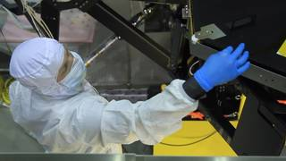 Technician in clean room suit working on Webb telescope