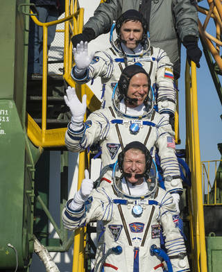 Three men in Sokol launch suits wave while standing on stairs leading up to Soyuz capsule