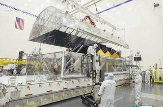 Engineers open the interior tent frame of the Space Telescope Transporter for Air, Road and Sea (STTARS) at Northrop Grumman.