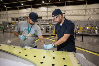 Lockheed Martin technicians working on the wing spar for NASA's X-59.