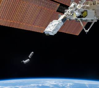 Two Dove small satellites shown deploying from the International Space Station.