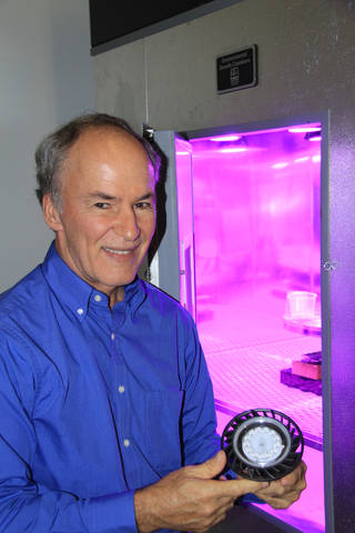 Dr. Ray Wheeler, lead for Advanced Life Support Research activities at Kennedy Space Center, holds a red and blue LED light fixt