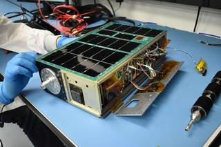 A cereal-box sized satellite with some wiring exposed sits on a table while someone with gloved hands works on it