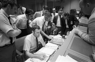 A group of flight controllers gathers around the console of Glenn S. Lunney (seated, nearest camera)