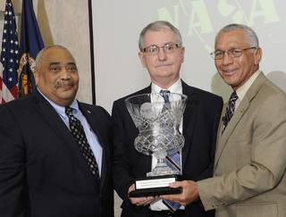 David Brock, center, accepts the NASA Small Business Administrator's Cup in 2015 from former NASA Administrator Charles Bolden.