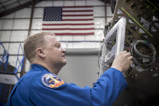 Astronaut Eric Boe examines hardware during a tour of the SpaceX facility in Hawthorne, California.