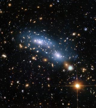 Immagine di Hubble dell'ammasso di galassie MACS J0416 che mostra una scena di cielo stellato con striscio blu centrale