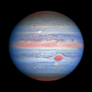 banded, red-white-and-blue-hued view of Jupiter in ultraviolet/visible/near-infrared light, as observed by Hubble