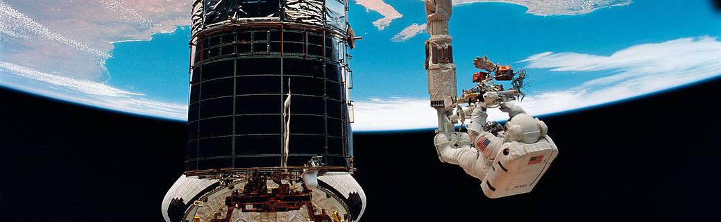 spacecraft in orbit around earth with astronaut