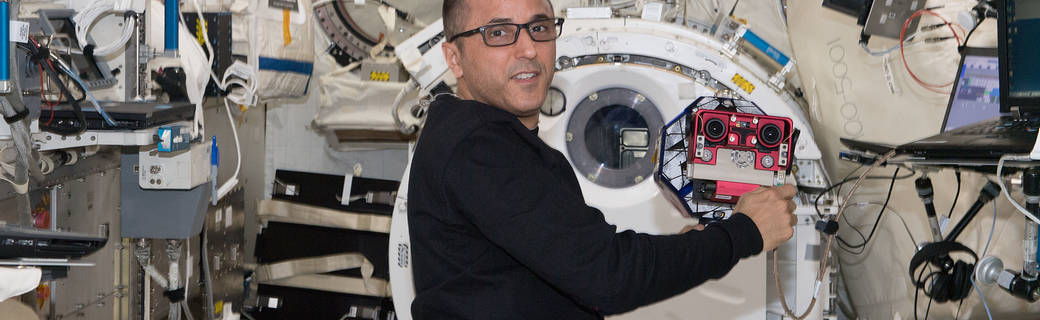NASA astronaut Joe Acaba works with the SPHERES satellite as part of the SmoothNav investigation.