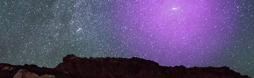 purple-hued glow in the night sky over rocky terrain: an illustration of Andromeda's halo