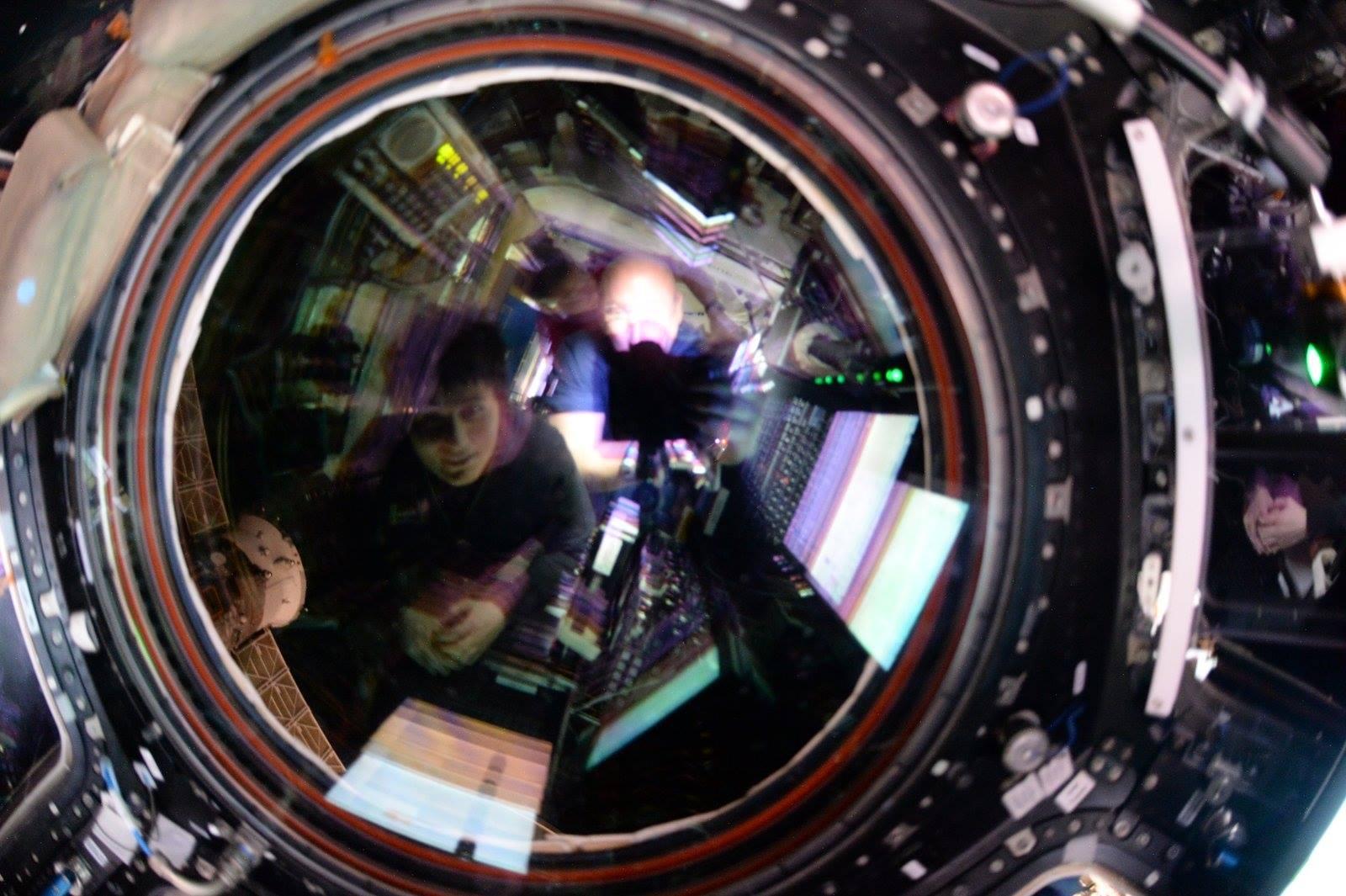 NASA Astronaut Scott Kelly And ESA Samantha Cristoforetti Reflected In Circular Lens Watching Spacecraft Arrival