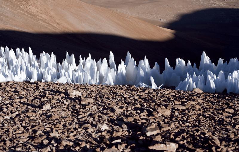 """Um exemplo dos penitentes do extremo sul da planície de Chajnantor no Chile. Embora essas formações de gelo atinjam apenas alguns metros de altura, enquanto o terreno com """"lâminas"""" de Plutão atinge centenas de metros, ambos possuem cumes afiados semelhantes. Crédito: Wikimedia Commons / ESO"""