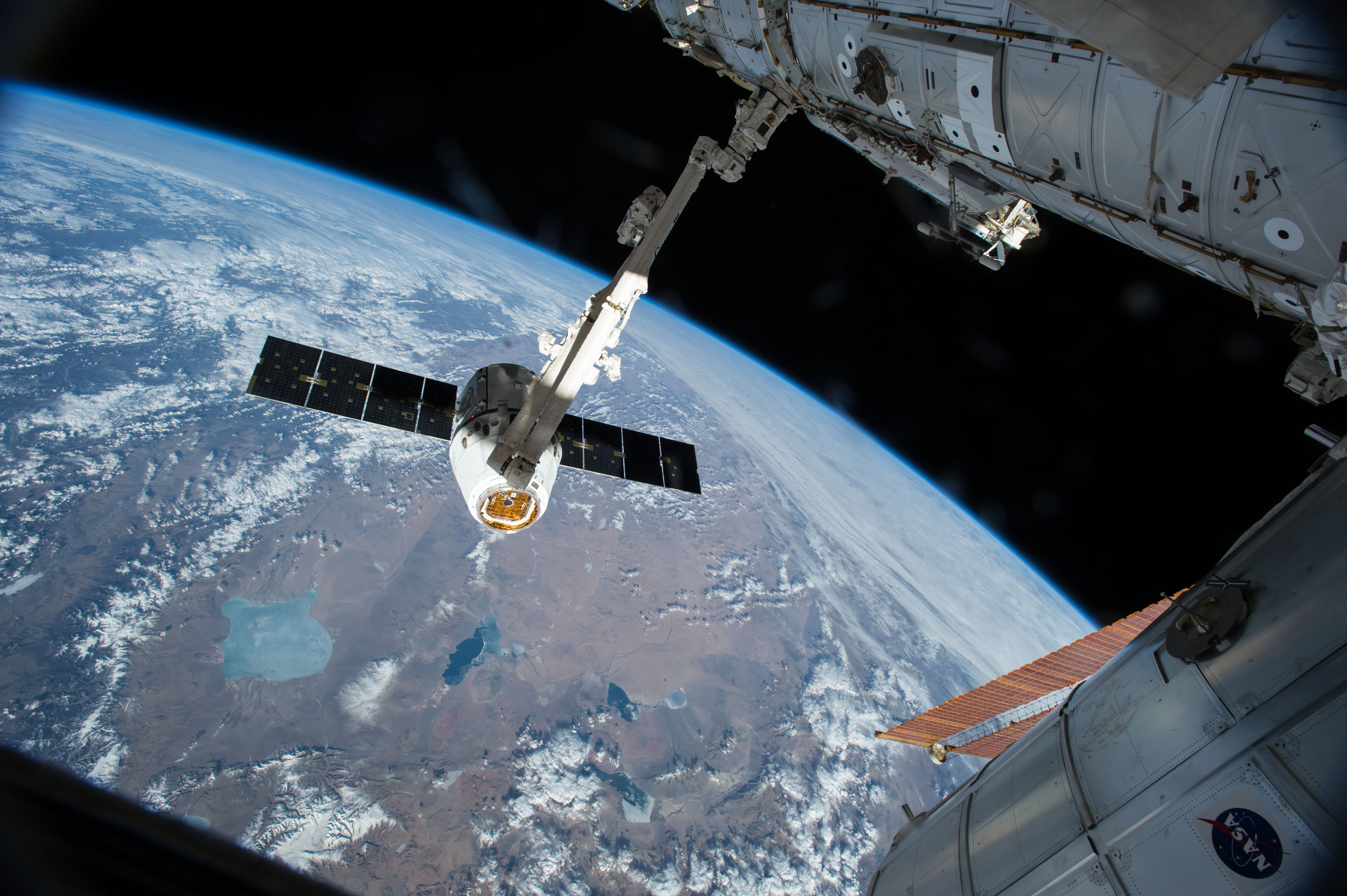 space station research the canadarm 2 reaches out to grapple the spacex dragon cargo spacecraft and prepare it to