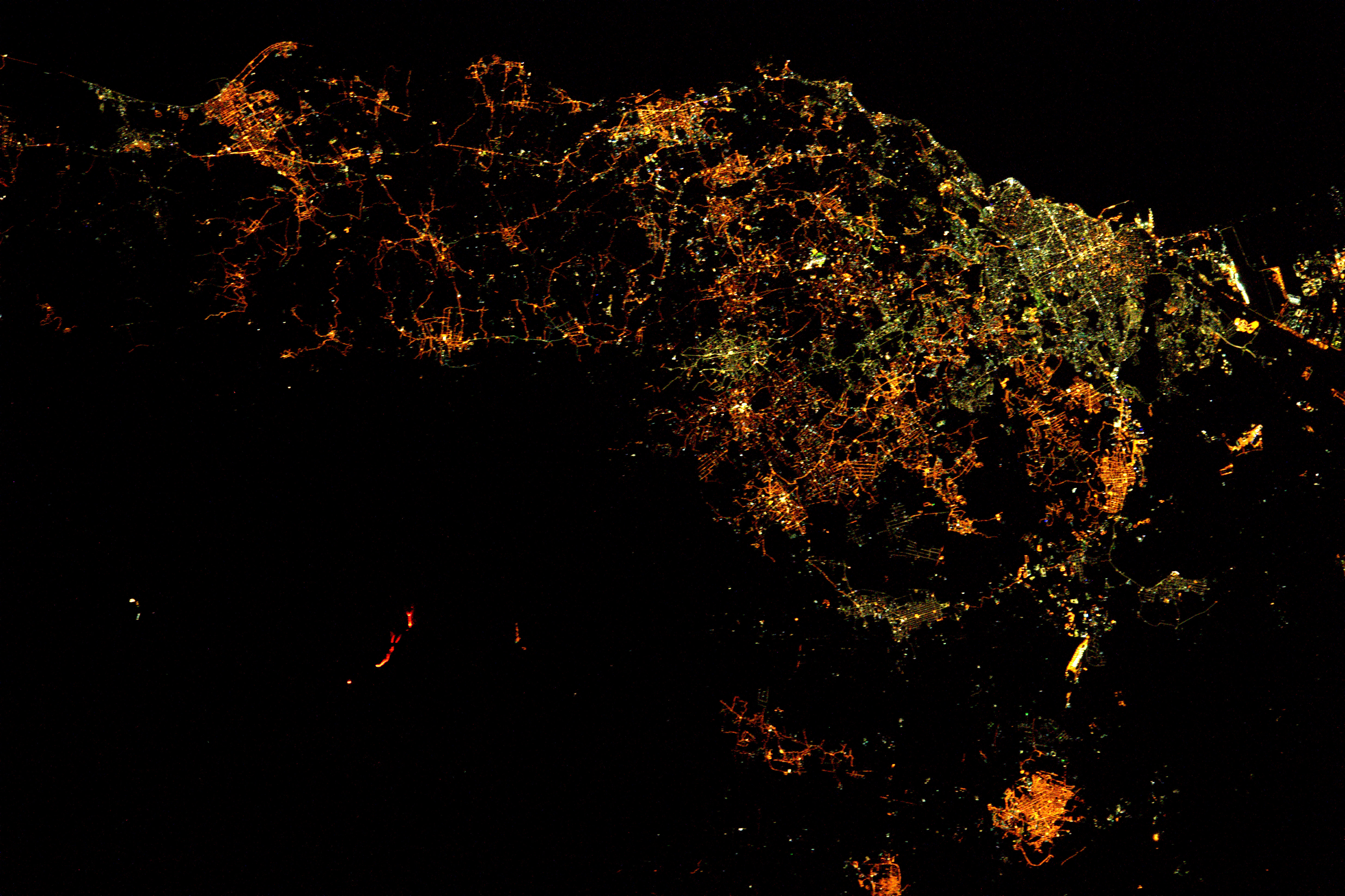 nighttime view from orbit of sicily with red lines showing volcano eruption