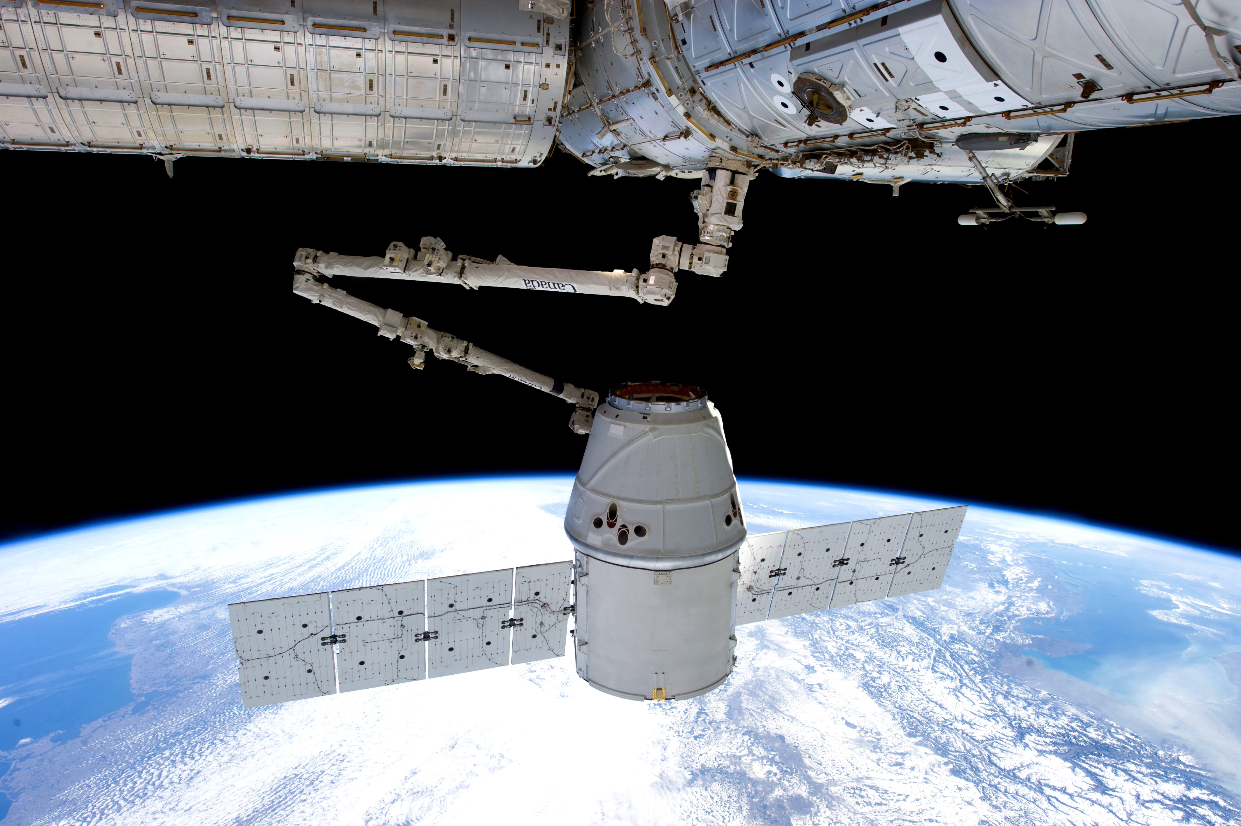 expedition 34 crew members aboard the international space station use a robotic arm to capture a spacex dragon capsule delivering supplies on march 3 2013