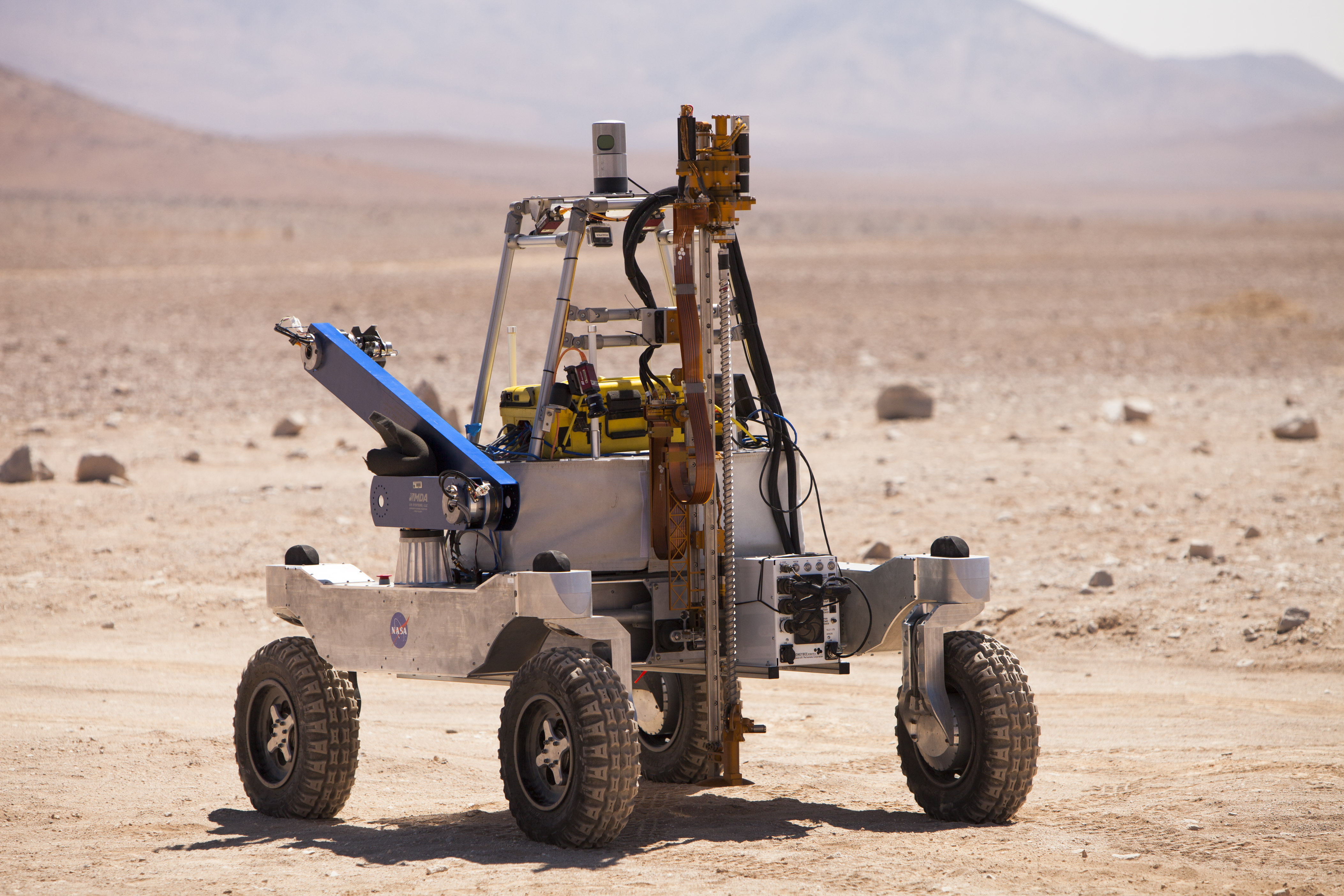 The Rover In Its Mobile Configuration With Drill Raised And Visible At The  Front, Arm