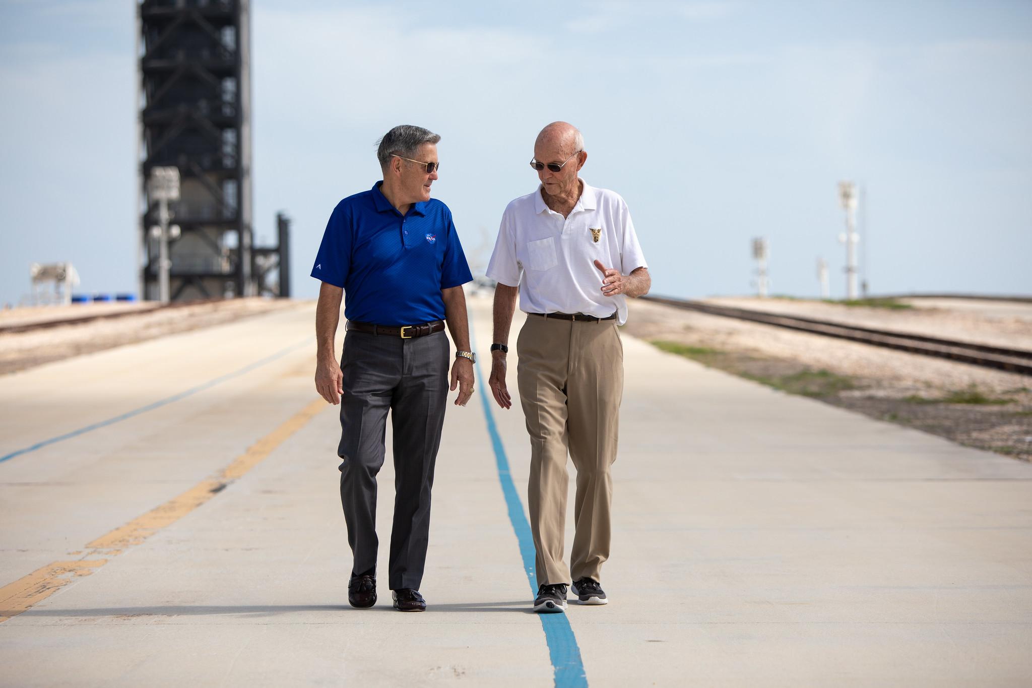 ไมเคิล คอลลินส์ (คนขวา) ภาพนี้ถ่ายเอาไว้ในวันที่ 16 กรกฎาคม ปี ค.ศ. 2019 ส่วนคนซ้ายคือผู้อำนวยการแห่งศูนย์อวกาศเคนเนดี บ๊อบคาบาน่า ณ ฐานปล่อยจรวด Launch Complex 39A ภาพโดย NASA/Frank Michaux