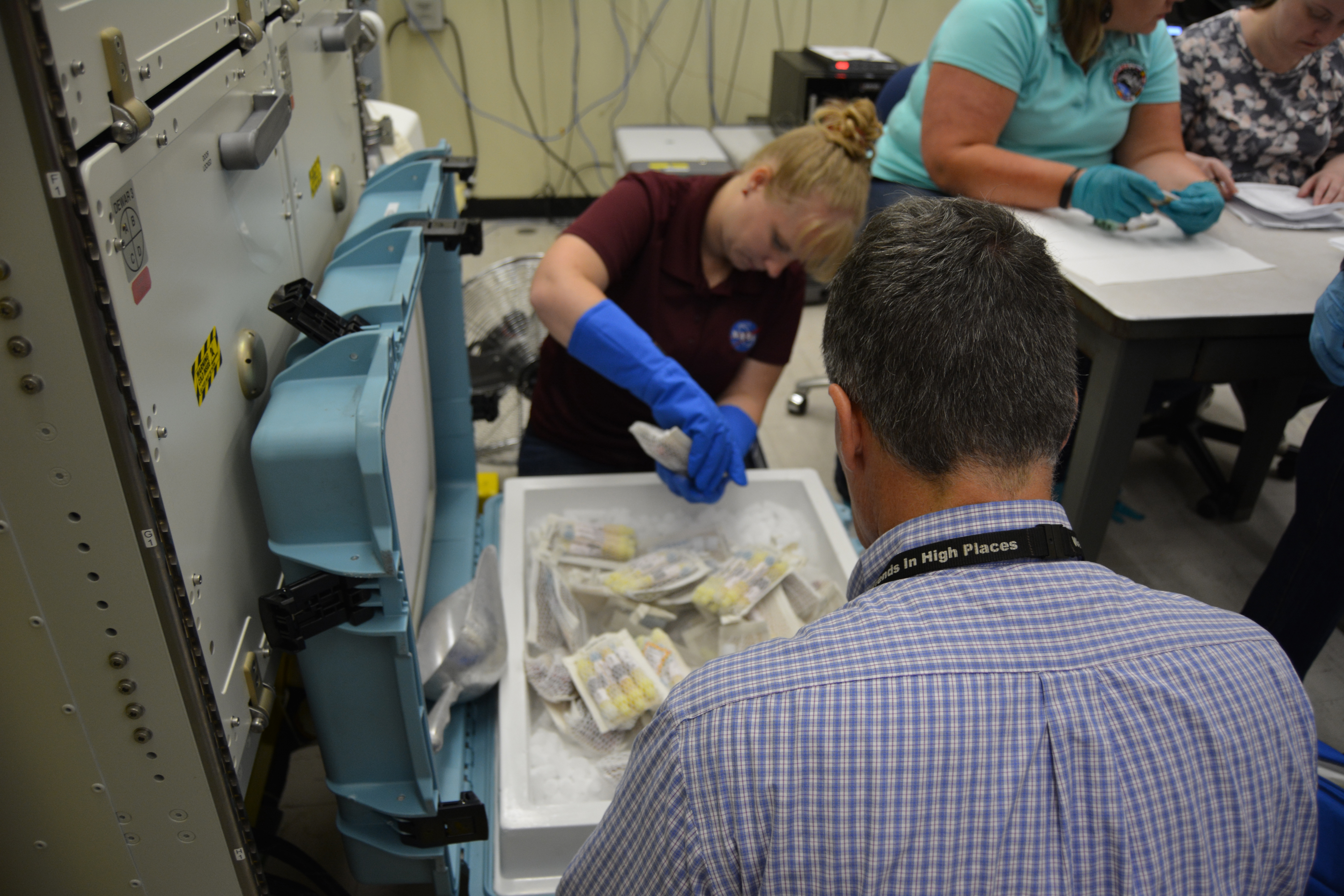 one if by land two if by space nasa space station · members of the cold stowage lab team unpack samples