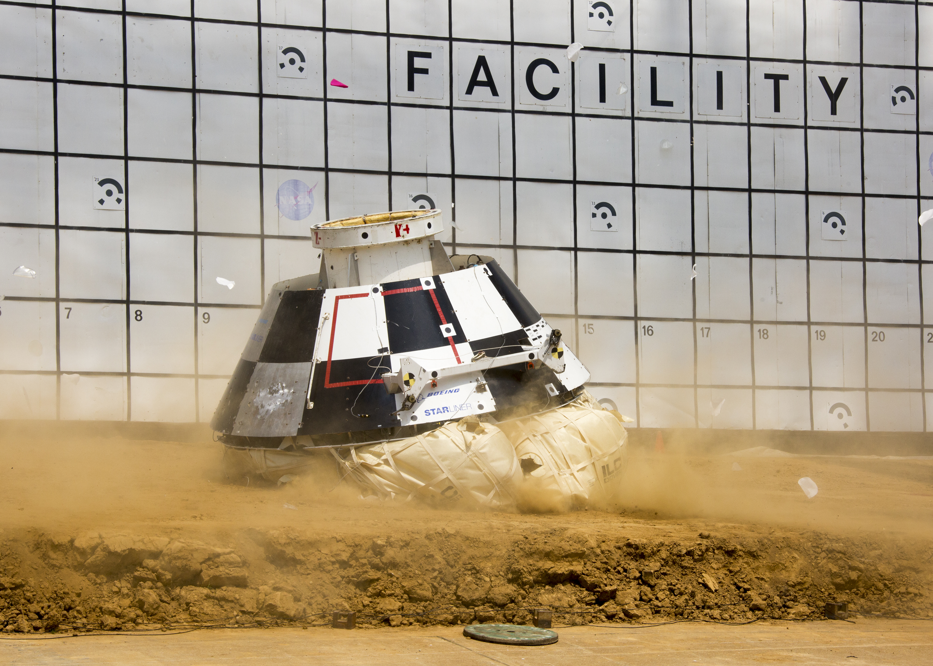 The Starliner mock-up hits the ground during landing system tests.