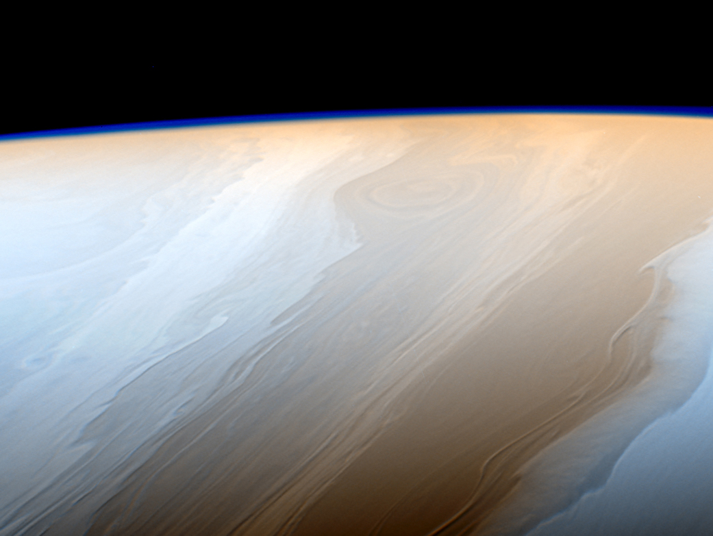 Of planet earth as a point of light between the icy rings of saturn - Clouds On Saturn