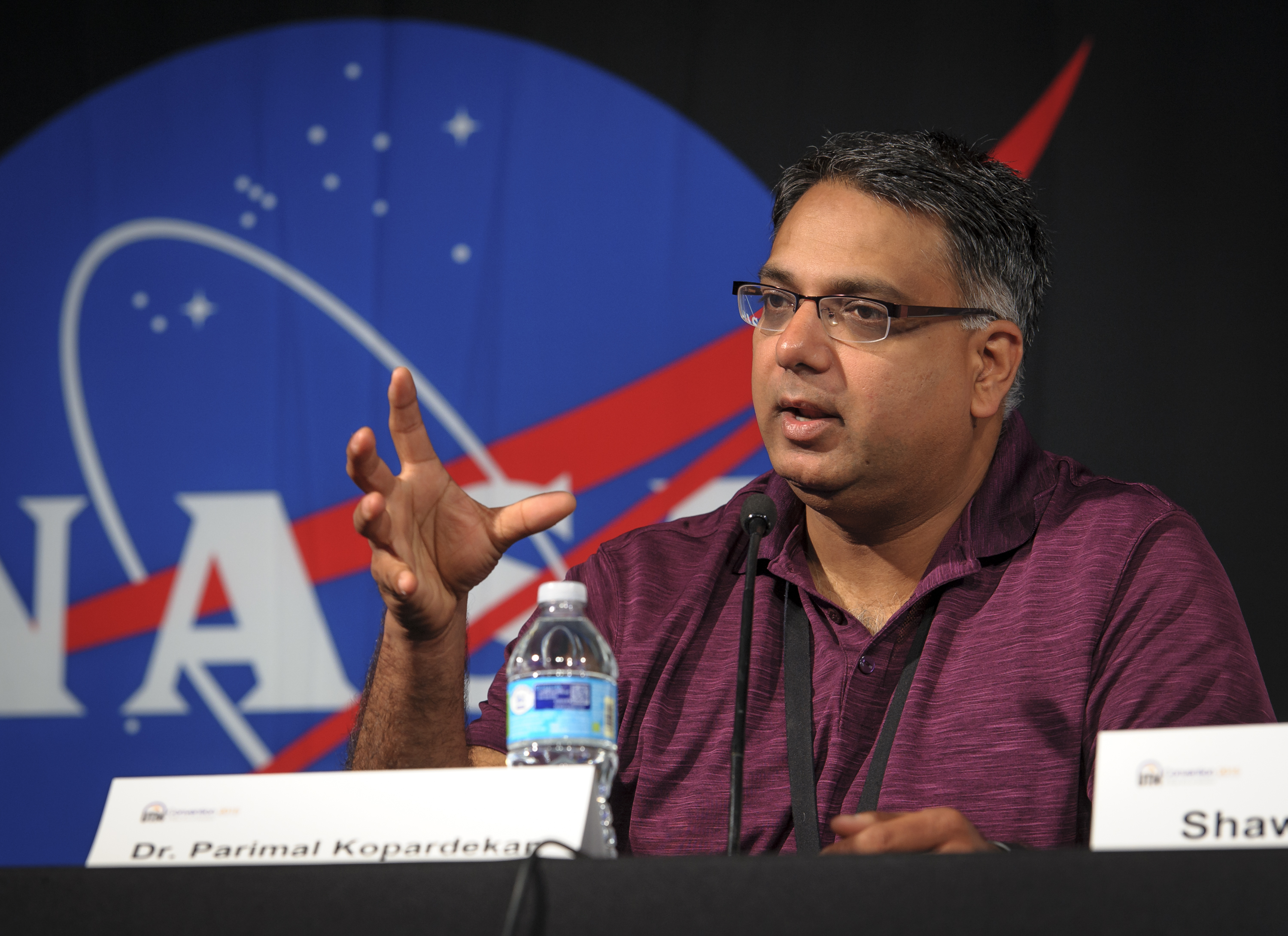 Photo of Parimal Kopardekar speaking in a panel discussion. A large NASA insignia is displayed in the background.