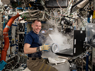 Cosmonaut Andrey Borisenko smiles while holding camera equipment inside the space station